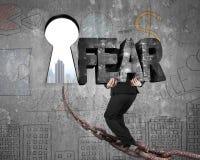 Mężczyzna przewożenia strachu słowo na łańcuchu w kierunku keyhole z pejzażem miejskim Obrazy Royalty Free