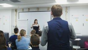 Mężczyzna przy biznesowym seminaryjnym mówieniem z wykładowcą i widownią - spotkania pojęcie obrazy royalty free