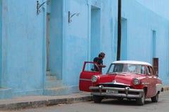 Mężczyzna przy czerwonymi samochodu i błękita ścianami Obrazy Royalty Free