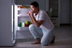 Mężczyzna przy fridge łasowaniem przy nocą Obraz Stock