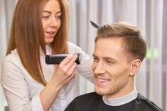 Mężczyzna przy fryzjera męskiego ono uśmiecha się obrazy stock