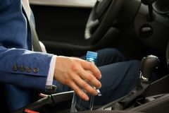 Mężczyzna przy kołem samochód, wziąć butelkę woda na drodze zdjęcie stock