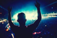 Mężczyzna przy koncertowym tanem przeciw światła tłu Sylwetka mężczyzna przy festiwalem muzyki obrazy stock