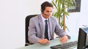 Mężczyzna przy opowiada na jego słuchawki jest biurkiem zdjęcie wideo
