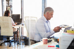 Mężczyzna przy pracą używać mądrze telefon, biurowy wnętrze Zdjęcie Stock
