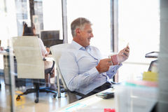 Mężczyzna przy pracą używać mądrze telefon, biurowy wnętrze Obraz Stock