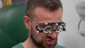 Mężczyzna przy przyjęciem oftalmologa oka egzamin wybór okularowi obiektywy i zdjęcie wideo
