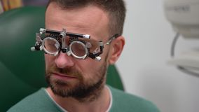 Mężczyzna przy przyjęciem oftalmologa oka egzamin wybór okularowi obiektywy i zbiory wideo