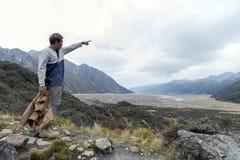 Mężczyzna przy punktem widzenia wzdłuż odprowadzenie śladu Błękitni jeziora i Tasman lodowa widokiem w Aoraki, góra Kucbarskim pa zdjęcie stock