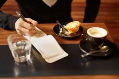Mężczyzna przy sklep z kawą z kawy espresso i ciasta writing Zdjęcia Royalty Free
