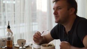 Mężczyzna przy stołem w kawiarni je jarzynowej sałatki zdjęcie wideo