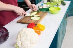 Mężczyzna przygotowani warzywa dla kulinarnego jarzynowego ragout Zamyka up kalafior i papryka na bielu stole Mężczyzna tnący zuc obrazy royalty free