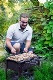 Mężczyzna przygotowywa grilla w ogródzie Zdjęcie Stock