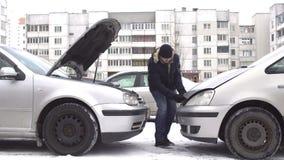 Mężczyzna przygotowywa samochodowego dawcy zaczynać samochód z dymisjonowaną baterią w zimie, skoku początek, accumulator zdjęcie wideo