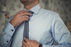 Mężczyzna przystosowywa jego krawat Zdjęcia Stock