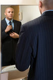 Mężczyzna przystosowywa jego krawat w lustrze Zdjęcie Stock