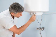 Mężczyzna przystosowywa temperaturę elektryczny bojler zdjęcie royalty free