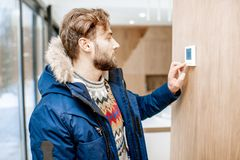 Mężczyzna przystosowywa temperaturę z cieplarką w domu zdjęcia stock