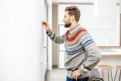 Mężczyzna przystosowywa temperaturę z cieplarką w domu zdjęcie stock