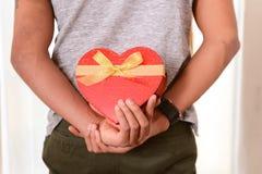 Mężczyzna pudełka hidding serce kształtująca teraźniejszość Obraz Stock