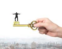 Mężczyzna równowaga na skarbu kluczu w funta znaka kształcie Obraz Royalty Free