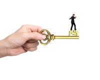 Mężczyzna równowaga na skarbu kluczu w funta znaka kształcie Zdjęcie Stock