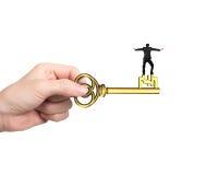 Mężczyzna równowaga na skarbu kluczu w funta znaka kształcie Obrazy Stock
