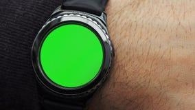 Mężczyzna ręk gesty na round parawanowym nowożytnym smartwatch z zielenieją parawanową chroma klucza zawartość zbiory