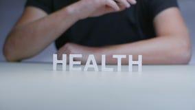 Mężczyzna ręk składu słowa zdrowie od białego klingerytu listu na szarym tle zbiory wideo