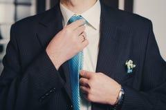 Mężczyzna ręk zbliżenie wiąże jego krawat kępkę obrazy stock
