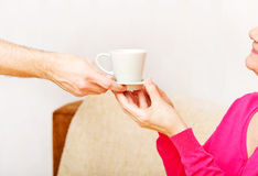 Mężczyzna ręka daje filiżance herbata lub kawa starsza kobieta Zdjęcia Royalty Free