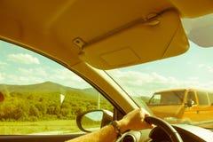 Mężczyzna ręka na kierownicie, samochód jedzie wzdłuż drogi przeciw tłu zielona trawa i góry, kierowca jest zapalony i cieszy się obrazy stock