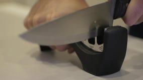 Mężczyzna ręka ostrzy nóż na ostrzarce zbiory wideo