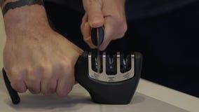 Mężczyzna ręka ostrzy nóż na ostrzarce zbiory