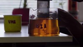 Mężczyzna ręka podnosi w górę i stawia puszka herbacianego zbiornika szklany herbaciany garnek umieszczający na stole zbiory