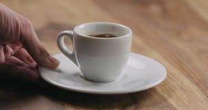 Mężczyzna ręka przynosi filiżankę świeża kawa espresso na drewno stole fotografia stock