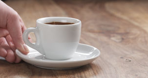 Mężczyzna ręka przynosi filiżankę świeża kawa espresso na stole Fotografia Stock