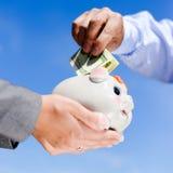 Mężczyzna ręka stawia dolary w piggybank mieniu obok Zdjęcia Stock