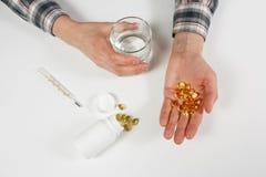 Mężczyzna ręka trzyma żółte lekarstwo kapsuły omega 3 Obrazy Royalty Free