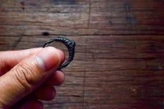 Mężczyzna ręka trzyma czerń pierścionek z zamazanym drewnianym tłem Zdjęcia Royalty Free