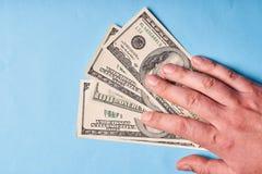 Mężczyzna ręka trzyma dolary, odgórny widok niebieska tła obrazy royalty free