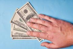 Mężczyzna ręka trzyma dolary, odgórny widok niebieska tła fotografia stock