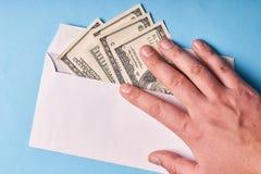 Mężczyzna ręka trzyma dolary w kopertowym, odgórnym widoku, niebieska tła obrazy royalty free