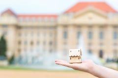 Mężczyzna ręka trzyma drewnianego modela dom nad plama budynkiem Zdjęcie Royalty Free