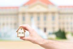 Mężczyzna ręka trzyma drewnianego modela dom nad plama budynkiem Zdjęcie Stock