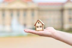 Mężczyzna ręka trzyma drewnianego modela dom nad plama budynkiem Fotografia Stock