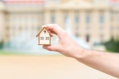 Mężczyzna ręka trzyma drewnianego modela dom nad plama budynkiem Obrazy Stock