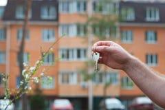 Mężczyzna ręka trzyma klucze mieszkanie na tle multistory budynek Fotografia Stock
