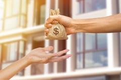 Mężczyzna ręka trzyma pieniądze daje inna osoba dla kupować r obrazy stock