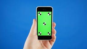 Mężczyzna ręka trzyma smartphone w pionowo pozycji Zielony ekran na b??kitnym chromakey i telefonie ?adny gestykulowa? zbiory wideo